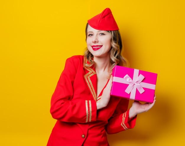 Stewardess dragen in rode uniform met vakantie gfit box