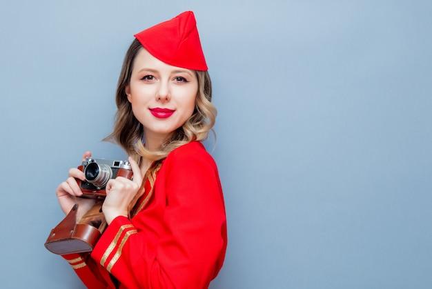Stewardess dragen in rode uniform met vintage camera