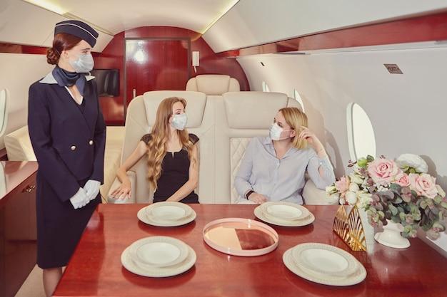 Stewardess in gezichtsmasker bedient passagiers in business class in vliegtuig