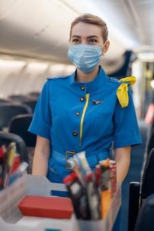 Stewardess met beschermend gezichtsmasker die wegkijkt en voedsel serveert aan passagiers in vliegtuigen. luchtstewardess die met karretje op gangpad loopt. reizen, service, transport, vliegtuigconcept