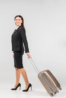 Stewardess met koffer die zich omdraait