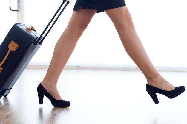 Stewardessbenen met bagage in luchthaven.