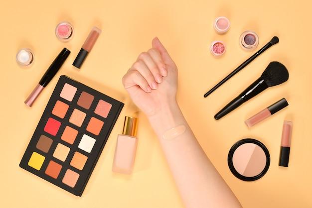 Stichting aan de kant van de vrouw. professionele make-upproducten met cosmetische schoonheidsproducten, foundation, lippenstift, oogschaduw, borstels en gereedschap.