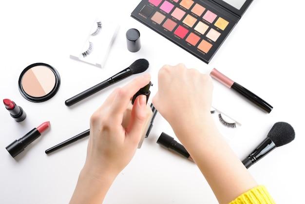 Stichting in handen van de vrouw. professionele make-upproducten met cosmetische schoonheidsproducten, foundation, lippenstift, oogschaduw, wimpers, borstels en gereedschap.