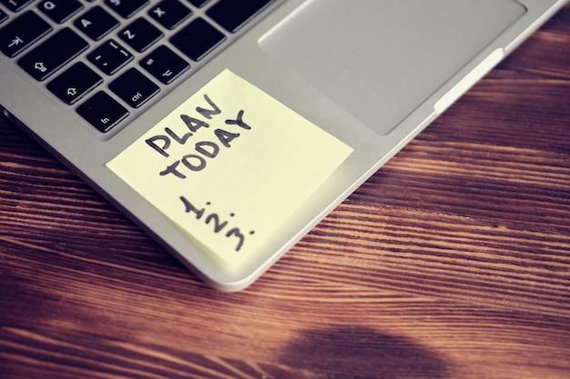 Sticker met de inscriptie - het plan voor vandaag is gelijmd op de laptop op een houten achtergrond.