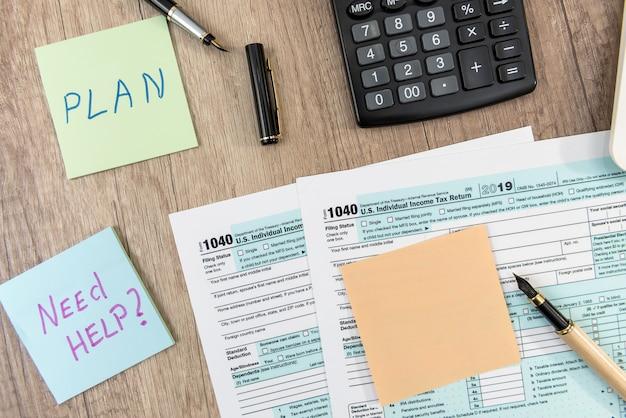 Sticker met tekst hulp nodig rekenmachine en 1040 belastingformulier op kantoor. fiscaal concept