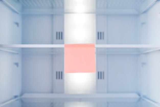 Sticker op de plank van een lege koelkast.