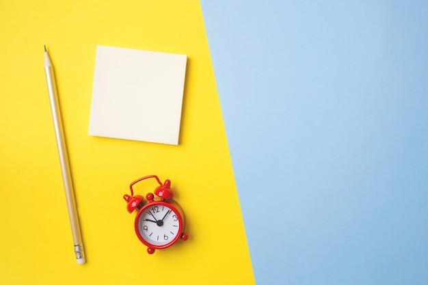 Stickers briefpapier en een klok op een geel blauwe tafel