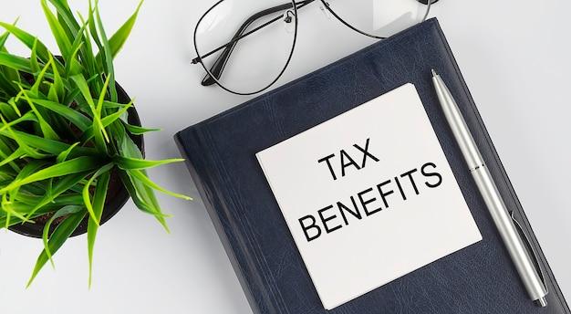 Stickers op notitieboekjestekst belastingvoordelen met pen en bril op de witte achtergrond