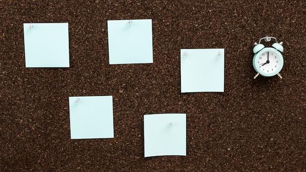 Sticky notes opknoping en klok op cork board. terug naar school-concept. werken vanuit huis en timemanagement.