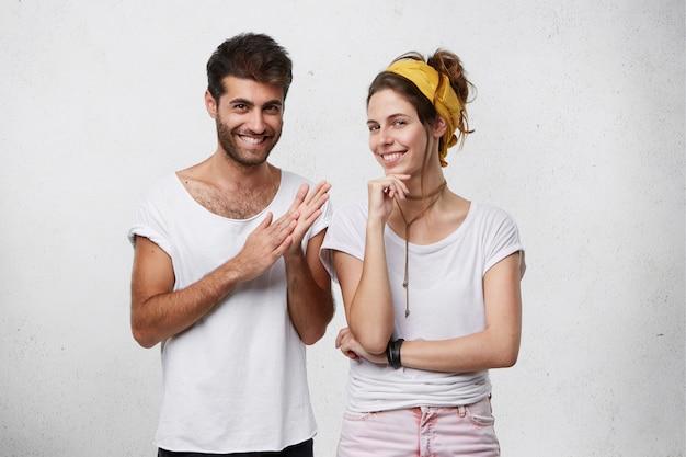 Stiekeme sluwe en sluwe jonge europese man en vrouw gekleed in stijlvolle kleding kijken met mysterieuze glimlach, man maakt gebaar alsof hij zijn handen wast