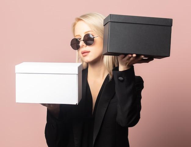 Stijl blond in blazer en zonnebril met geschenkdozen op roze
