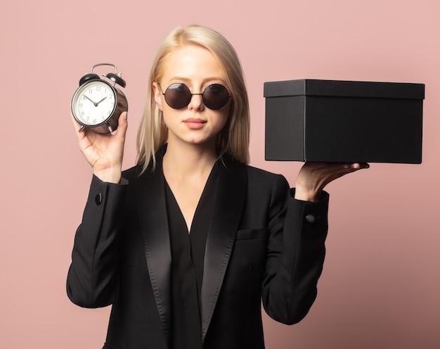 Stijl blond in blazer en zonnebril met zwarte geschenkdoos en wekker op roze