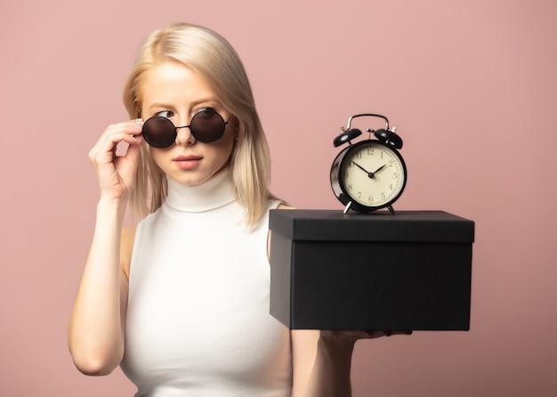 Stijl blond in top en zonnebril met wekker en zwarte geschenkdoos op roze