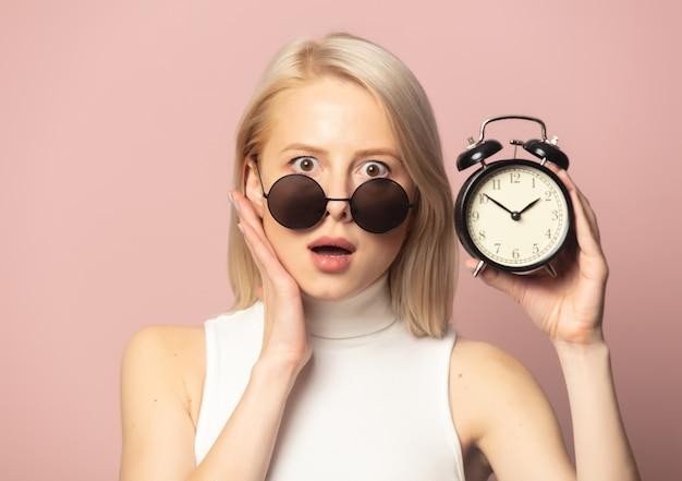 Stijl blond in top en zonnebril met wekker op roze
