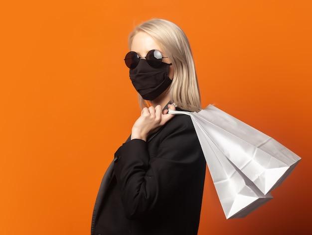 Stijl blond in zwarte blazer met boodschappentassen op uitbundig oranje