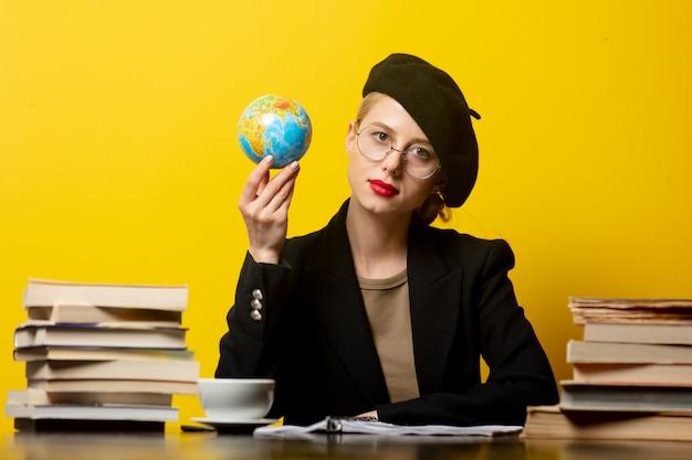 Stijl blonde vrouw in baret zittend aan tafel met boeken rond en houdt wereldbol op geel