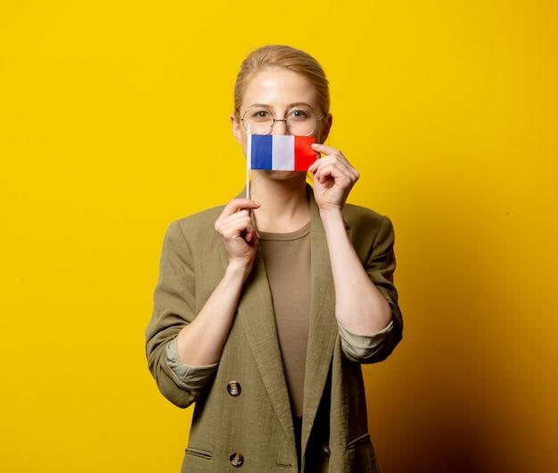 Stijl blonde vrouw in jas met franse vlag op geel