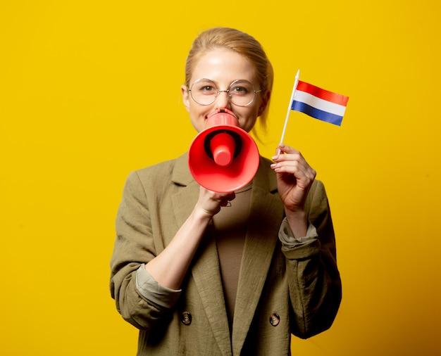 Stijl blonde vrouw in jas met nederlandse vlag en megafoon op geel