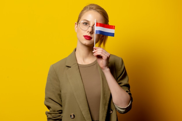 Stijl blonde vrouw in jas met nederlandse vlag op geel
