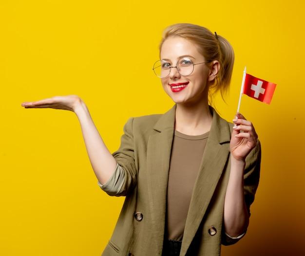 Stijl blonde vrouw in jas met zwitserse vlag op geel