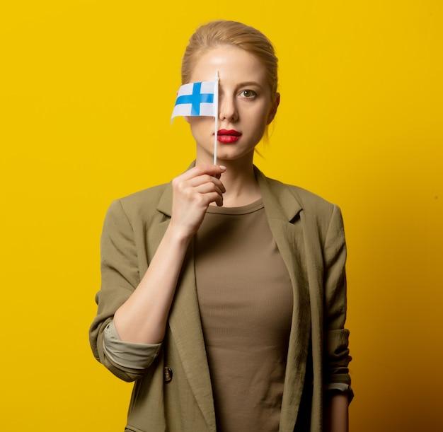 Stijl blonde vrouw in jasje met finse vlag op geel