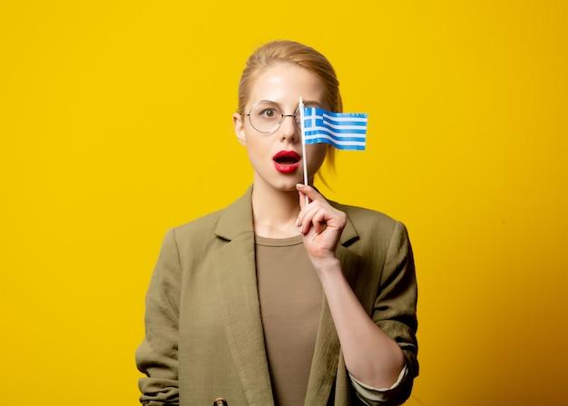 Stijl blonde vrouw in jasje met griekse vlag op geel
