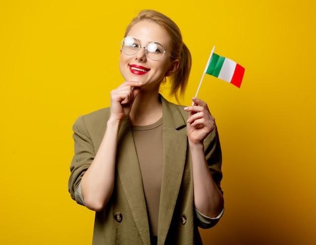 Stijl blonde vrouw in jasje met italiaanse vlag op geel Premium Foto