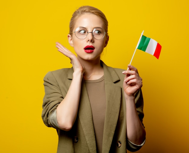 Stijl blonde vrouw in jasje met italiaanse vlag op geel