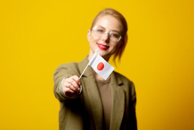 Stijl blonde vrouw in jasje met japanse vlag op geel