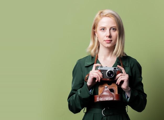 Stijl blonde vrouw in mantel met camera