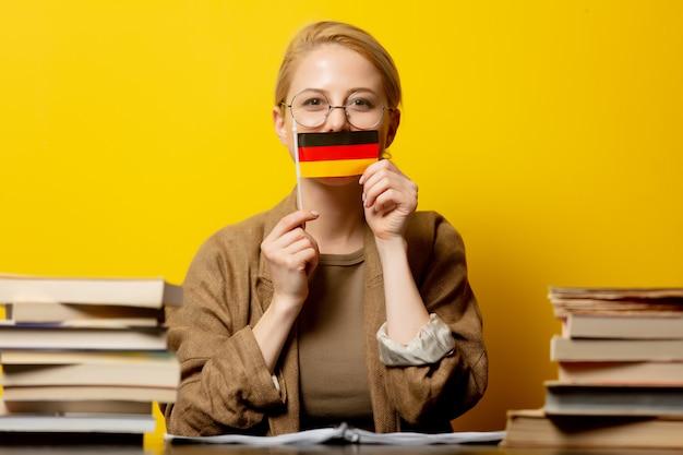 Stijl blonde vrouw zitten aan tafel met boeken en vlag van duitsland op geel