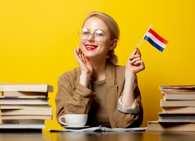 Stijl blonde vrouw zitten aan tafel met boeken en vlag van nederland op geel