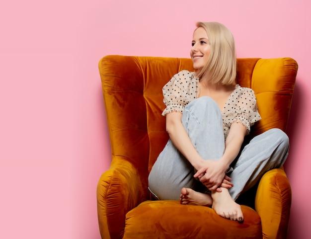 Stijl blonde vrouw zitten in een vintage fauteuil op roze muur