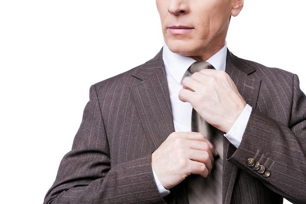 Stijl en succes. bijgesneden afbeelding van zelfverzekerde volwassen man in formalwear die zijn stropdas aanpast terwijl hij tegen een witte achtergrond staat