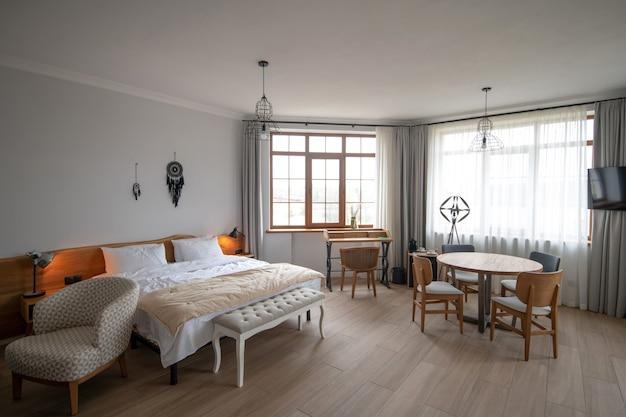 Stijl. grote lichte kamer met witte muren en plafond met licht meubilair in nieuw huis met daglicht