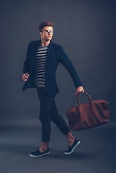 Stijl in actie. volledige lengte van zelfverzekerde jonge knappe man in glazen draagtas en wegkijkend terwijl hij tegen een grijze achtergrond loopt