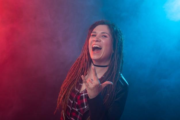 Stijl, jeugd, mensen concept - jonge vrouw met dreadlock ziet eruit als rocker