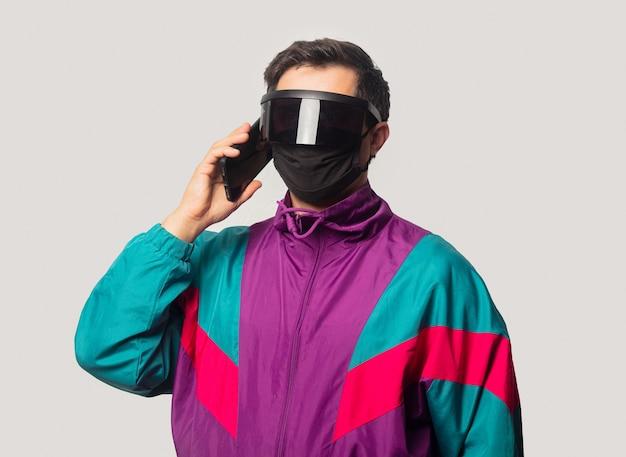 Stijl man gezichtsmasker en futuristische glassses met mobiele telefoon
