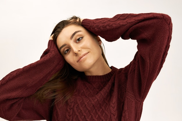 Stijl, mode, breigoed en seizoensconcept. portret van aantrekkelijke zelfverzekerde jonge europese vrouw gekleed in warme pullover hand in hand op haar hoofd, camera kijken met een gelukkige vrolijke glimlach