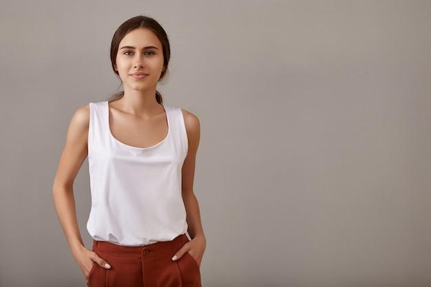 Stijl, mode, elegantie en vertrouwenconcept. stijlvolle jonge europese vrouw met blote gebruinde schouders poseren geïsoleerd tegen lege copyspace muur, met haar handen in de zakken