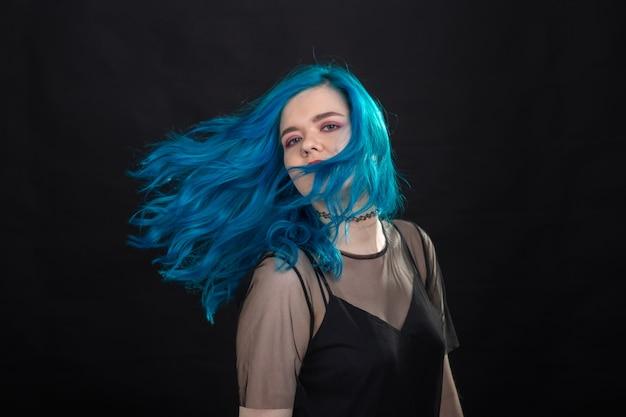 Stijl mode en haar concept close-up portret van een jonge vrouw in zwarte jurk met blauw haar
