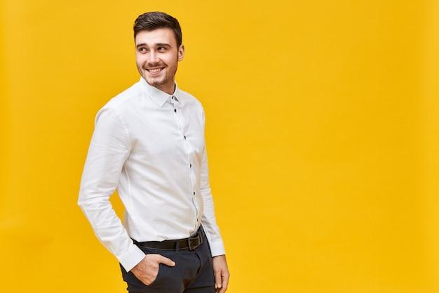 Stijl, mode en herenkledingconcept. knappe positieve jonge zakenman poseren geïsoleerd met hand in zak stijlvolle zwarte spijkerbroek, terugkijkend, met vrolijke gezichtsuitdrukking