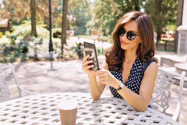 Stijl mooie vrouw met kort donker haar en charmante glimlach zit in de zomercafetaria in zonlicht met haar telefoon.
