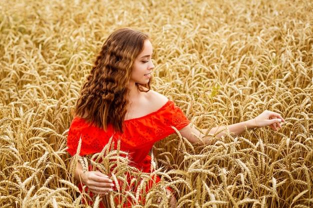Stijl roodharig meisje in rode jurk tay op geel tarweveld kaukasisch echt meisje gelukkige vrouw genieten van f...