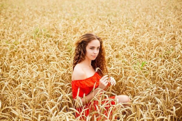Stijl roodharige dame in het rood kleden tay op gele tarwe natuur kaukasisch echt meisje portret van een schoonheid...