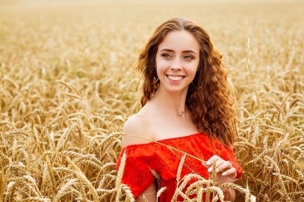 Stijl roodharige jonge vrouw in het rood kleden tay uitzicht gele tarwe natuur schattig meisje glimlacht met een sneeuwwitje...