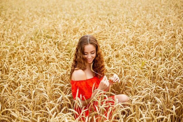 Stijl roodharige jonge vrouw in rode kleding op tarwe natuur gelukkig meisje met krullend haar in veld zoete sm...