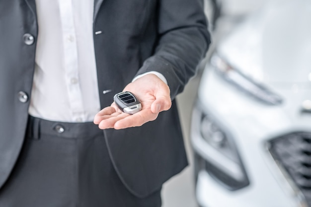 Stijl. stijlvolle autosleutelhanger liggend op uitgestrekte palm van man in donker pak, geen gezicht is zichtbaar