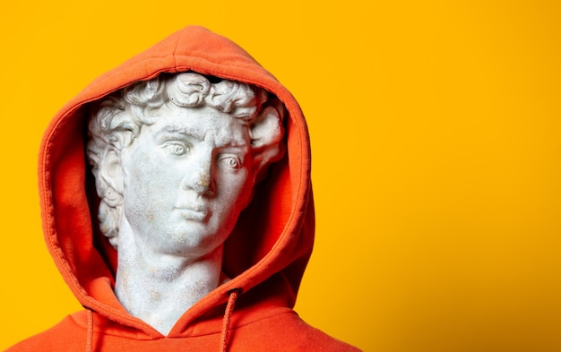 Stijl tienerjongen sculptuur in oranje hoodie op gele achtergrond